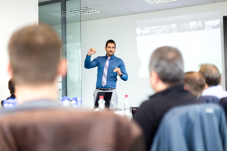 committee: Business man making a presentation at office. Business executive delivering a presentation to his colleagues during meeting or in-house business training, explaining business plans to his employees. Stock Photo