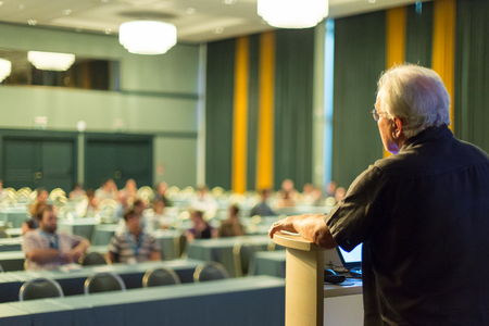 casualy: Casualy dressed senior professor giving talk at scientific conference. Audience at the conference hall. Research experts and entrepreneurship event. Stock Photo
