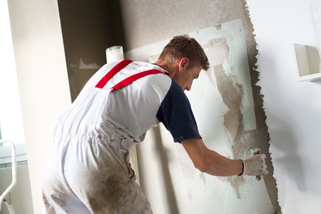 Thirty years old manual worker with wall plastering tools renovating house. Plasterer renovating indoor walls and ceilings with float and plaster. Zdjęcie Seryjne