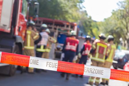 Team van blured brandweerlieden door brandweerwagen op beschermde plaats van het ongeluk. Focus op rode en witte veiligheid band.