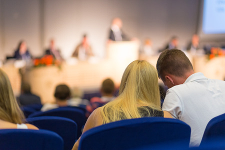Man and woman whispering in audience of business and entrepreneurship symposium. Speaker giving a talk at business meeting. Audience in the conference hall. Rear view of unrecognized participants. Stock Photo