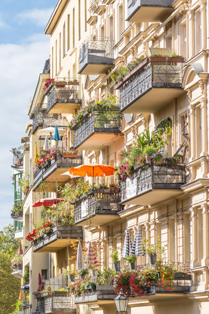 Traditional European residential house with balconys with colorful flowers and flowerpots. Kreuzberg neighborhood, Berlin, Germany, Stockfoto