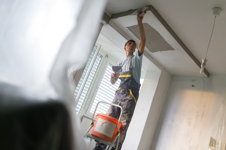 herramientas de construccion: Construction worker wearing worker overall with wall plastering tools renovating apartment house. Plasterer renovating indoor walls and ceilings with float and plaster. Construction finishing works.