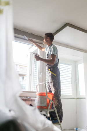 stucco: Construction worker wearing worker overall with wall plastering tools renovating apartment house. Plasterer renovating indoor walls and ceilings with float and plaster. Construction finishing works.