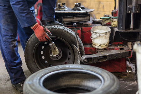 Professional auto mechanic replacing tire on wheel in car repair workshop. Stock Photo