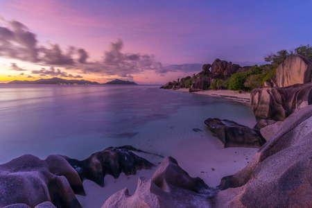 d'argent: Beautifully shaped granite boulders and a dramatic sunset at picture perfect tropical Anse Source dArgent beach, La Digue island, Seychelles. Stock Photo