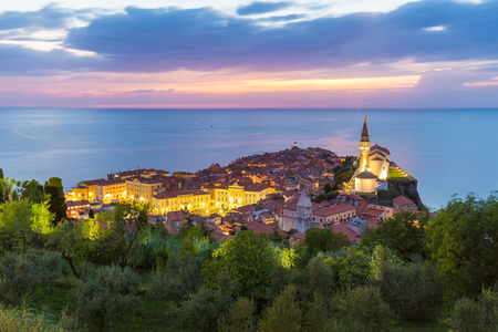 Romantic colorful sunset over picturesque old costal town Piran, Slovenia. Senic panoramic view. Stock Photo