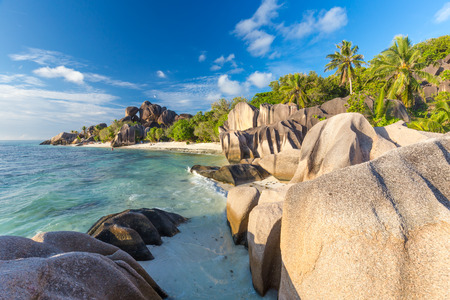 d'argent: Beautifully shaped granite boulders in illuminated by summer sun on picture perfect tropical Anse Source dArgent beach, La Digue island, Seychelles. Stock Photo