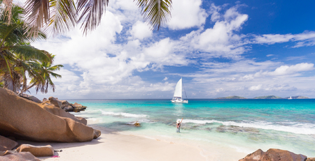 la digue: Woman wearing long floral summer dress and hat waving to people on the catamaran on Anse Patates beach, La Digue Island, Seychelles. Summer vacations on picture perfect tropical island concept.