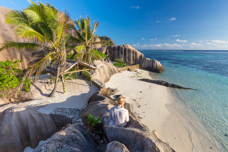 Female traveler emjoying amazing view of beautifully shaped granite boulders at picture perfect tropical Anse Source dArgent beach, La Digue island, Seychelles.