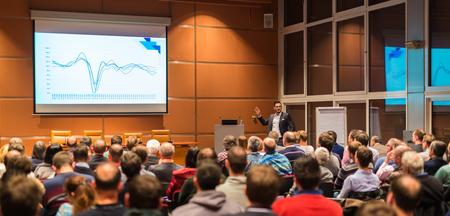 Spreker geeft een lezing in de conferentiezaal op zakelijke evenement. Publiek bij de conferentiezaal. Business and Entrepreneurship concept.