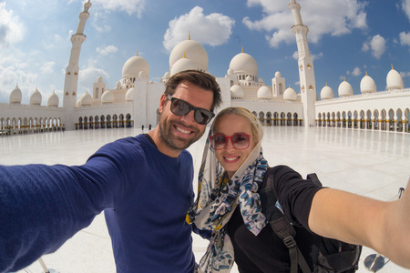 Tourist couple taking selfie in the courtyard of famous Sheikh Zayed Grand Mosque in Abu Dhabi, United Arab Emirates.