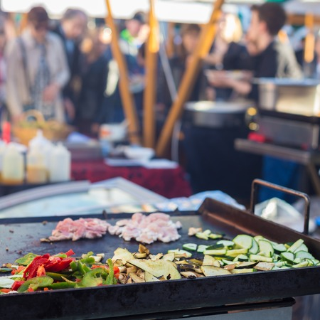 Chef making chicken with grilled vegetable tortilla wrap outdoor on street stall on Open kitchen international food festival event. Street food ready to serve on a food stall. Stock Photo