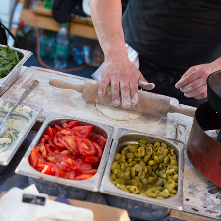 oudoor: Chef making pita bread for falafel roll outdoor on street stall on Open kitchen international food festival event in Ljubljana, Slovenia. Street food ready to serve on a food stall. Stock Photo