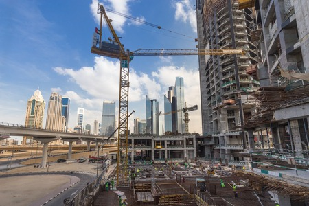 constraction: Laborers working on modern constraction site works in Dubai. Fast urban development consept.