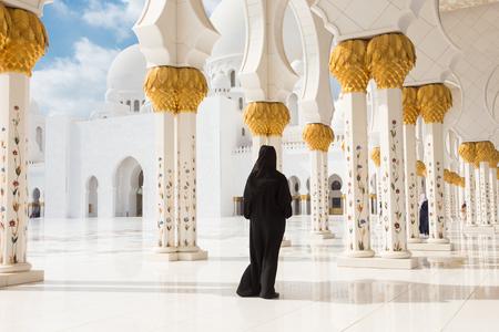 sacral: Traditionally dressed arabic woman wearing black burka wisiting Sheikh Zayed Grand Mosque in Abu Dhabi, United Arab Emirates.