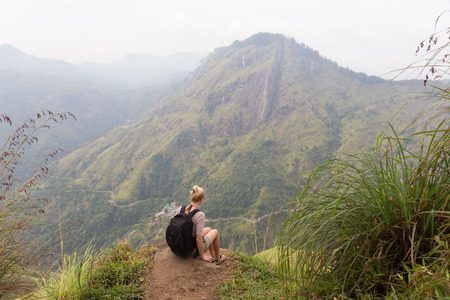 Woman enjoying pristine nature and beautiful view of tea plantations from the top of Small Adams peak near Ella, Sri Lanka. Tracking outdoors tourist adventure. Stock Photo