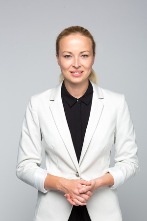 Portrait of cheerful, beautiful, smart, young businesswoman in white business attire, standing with arms crossed against gray background with arms steeple.