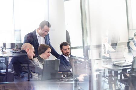 En milieu de travail dans le bureau moderne avec des gens d'affaires de remue-méninges. Homme d'affaires travaillant sur ordinateur portable lors de la réunion. Banque d'images - 70525624