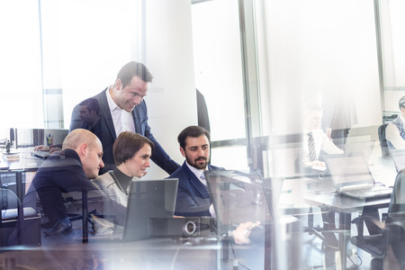 Workplace in modern office with business people brainstorming. Businessman working on laptop during the meeting.
