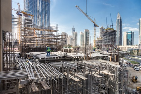 Laborers working on modern constraction site works in Dubai. Fast urban development consept.