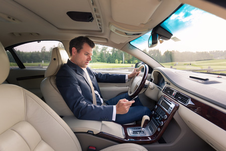 paying attention: Businessman using cell phone and texting while driving not paying attention to the road. Stock Photo