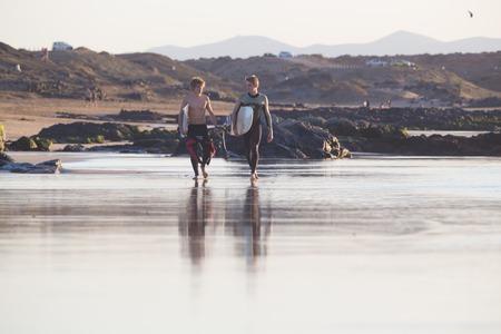 EL Cotillo, Spain - Dec 22, 2015:  Two surfers walking down El Cotillo beach, famous surfing destination on Fuerteventura, Canary Islands, Spain on December 22, 2015.