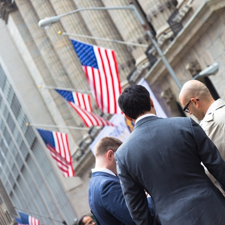 moneymaker: New York City, United States of America - March 26: Businessmen talking on Wall street in front of New York Stock Exchange on March 26, 2015.