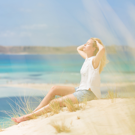 well being: Relaxed woman enjoying sun, freedom and life an a beautiful sandy beach of Balos in Greece. Young lady feeling free, relaxed and happy. Vacations, freedom, happiness, enjoyment and well being.