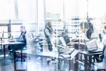 Arbeitsplatz in modernen Unternehmenszentrale mit Geschäftsleuten auf ihren Laptops arbeiten. Fenster Reflexionen. Business and Entrepreneurship Konzept.