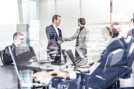Sealing a deal. Business people shaking hands, finishing up meeting in corporate office. Businessmen working on laptop seen in glass reflection. Business and entrepreneurship concept. Foto de archivo