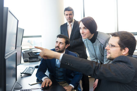 computer screens: Business team looking at data on multiple computer screens in corporate office. Businessman pointing on screen. Business people trading online. Business, entrepreneurship and team work concept. Stock Photo