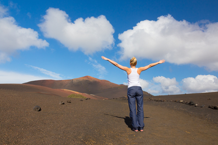 Woman hiking in nature can see the peak of Timanfaya volcano, nearly made it to top.