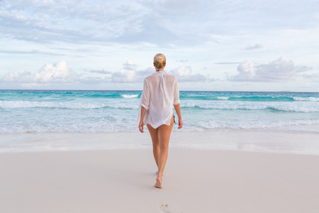summer beach: Woman wearing white loose tunic over bikini on Mahe Island, Seychelles. Summer vacations on picture perfect tropical beach concept.
