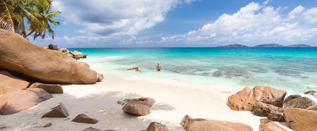 playas tropicales: Hombre deportivo activo vistiendo traje de baño negro disfrutando de la natación y el buceo en la playa magnífica de Anse Patates en La Digue Island, Seychelles. Las vacaciones de verano en concepto de imagen perfecta playa tropical.
