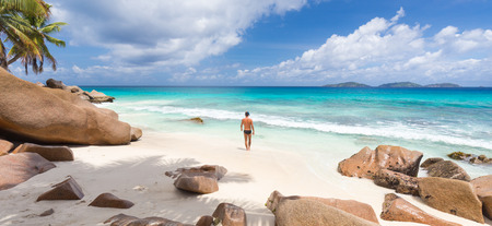 la digue: Active sporty man wearing black swimsuit enjoying swimming and snorkeling at amazing on Anse Patates beach on La Digue Island, Seychelles. Summer vacations on picture perfect tropical beach concept.