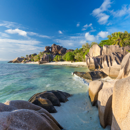 Beautifully shaped granite boulders in illuminated by summer sun on picture perfect tropical Anse Source dArgent beach, La Digue island, Seychelles. Stock Photo