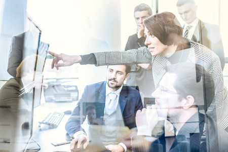 Equipo de negocios que buscan en los datos sobre múltiples pantallas de ordenador en la oficina corporativa. Empresaria que señala en la pantalla. La gente de negocios de comercio en línea. Negocio, el espíritu empresarial y el concepto de trabajo en equipo. Foto de archivo - 72164611