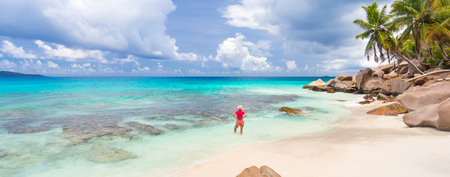 Woman wearing retro striped bikini and beach hat, enjoying amazing view on Anse Patates beach on La Digue Island, Seychelles. Summer vacations on picture perfect tropical beach concept. Stock Photo