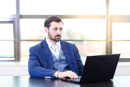 Portrait of successful corporate businessman in bright modern office focused on data on his laptop computer. Business and entrepreneurship concept. Stock Photo