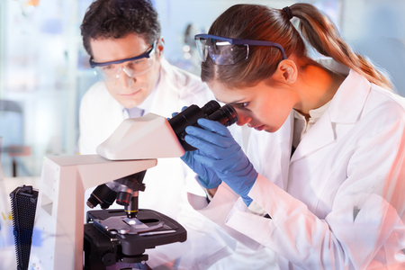 doctoral: Life scientists researching in laboratory. Female young scientist and her post doctoral supervisor microscoping in their working environment. Healthcare and biotechnology.