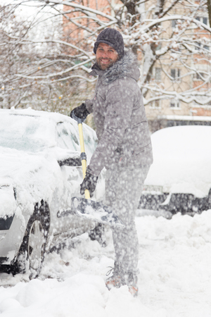 Man shoveling her parking lot after a winter snowstorm. Stock Photo
