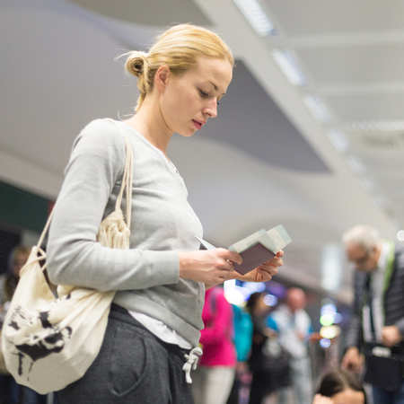 casualy: Casualy dressed woman checking flight informations on airplane ticket while waiting for her flight at airport.
