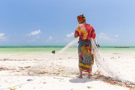Traditional african local rural fishing on Paje beach, Zanzibar, Tanzania. Traditionally dressed local woman pulling fishing net, catching small fish.