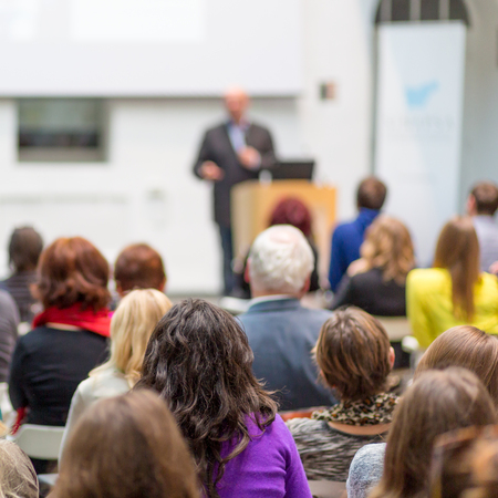 Audience at the conference hall. Speaker giving a talk on corporate Business Conference. Business and Entrepreneurship event. Stock Photo