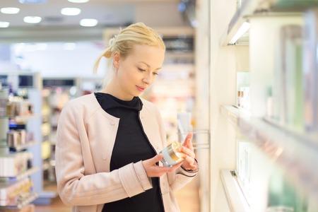 jeune blonde élégante femme de choisir un parfum dans un magasin de détail. test Belle dame blonde et l'achat de cosmétiques dans un magasin de beauté. Banque d'images