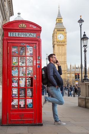 mobile telephone: Casual man talking on mobile phone in London, leaning on traditional british red telephone booth. Big Ben can be seen in background. London, England.