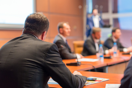 Manager giving a talk on corporate business event. Company managemant taking decisions at board room. Business and Entrepreneurship event. Focus on unrecognizable businessman in front.