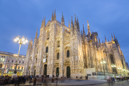 square image: Milan Cathedral, Duomo di Milano. Famous gothic cathedral church of Milan, Italy, Europe. Black and white image shot at dusk from square full of people.