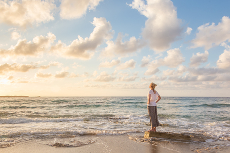 feeling happy: Relaxed woman enjoying sun, freedom and life an beautiful beach in sunset. Young lady feeling free, relaxed and happy. Concept of vacations, freedom, happiness, enjoyment and well being. Stock Photo